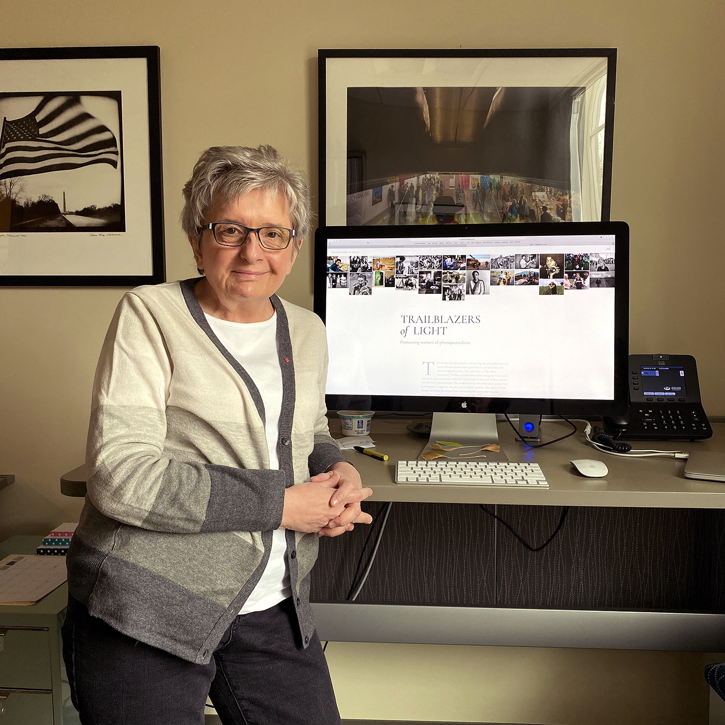 Marcy Nighswander stands in front of a monitor with the trailblazers of light website